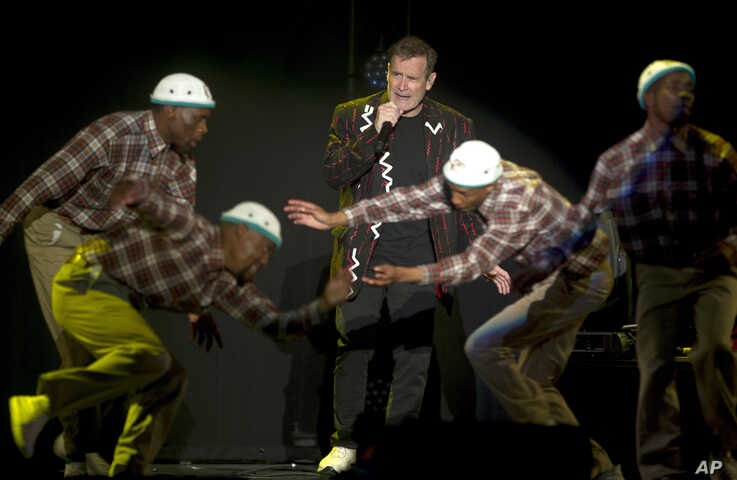 """In this photo taken Saturday, July 2017, South African musician Johnny Clegg, middle, and the dancers perform during """"The Final Journey"""" concert at the Grand Arena in Cape Town, South Africa."""