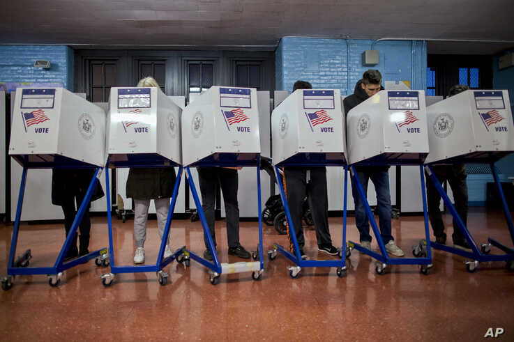 FILE - Voters fill out their forms as they prepare to vote at a polling station in the Brooklyn borough of New York, Nov. 8, 2016.