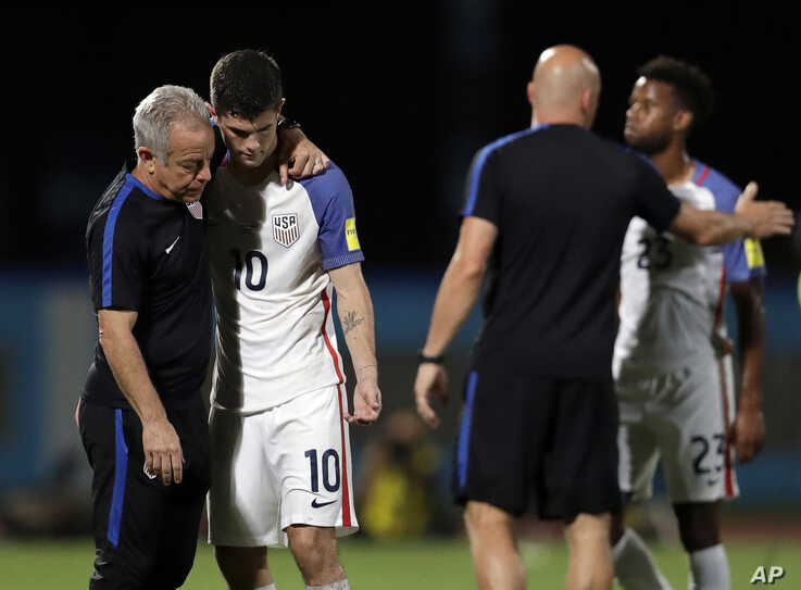 FILE - In this Oct. 10, 2017, file photo, United States' Christian Pulisic, (10) is comforted by assistant coach Dave Sarachan after losing 2-1 against Trinidad and Tobago during a 2018 World Cup qualifying soccer match  in Couva, Trinidad.