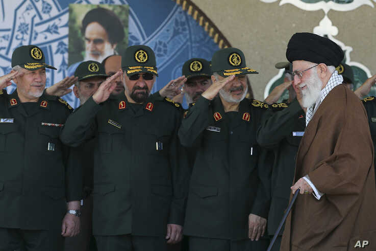 FILE- In this picture released by an official website of the office of the Iranian supreme leader, Supreme Leader Ayatollah Ali Khamenei, right, arrives at a graduation ceremony of the Revolutionary Guard's officers, in Tehran, Iran.