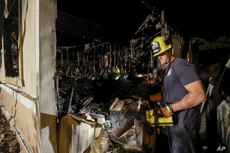 A fireman looks over a home Saturday, July 6, 2019 that burned after a earthquake in Ridgecrest, Calif.