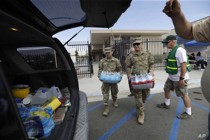 Members of the National Guard load water onto an SUV in the aftermath of an earthquake outside Trona High School in Trona, Calif., July 7, 2019.