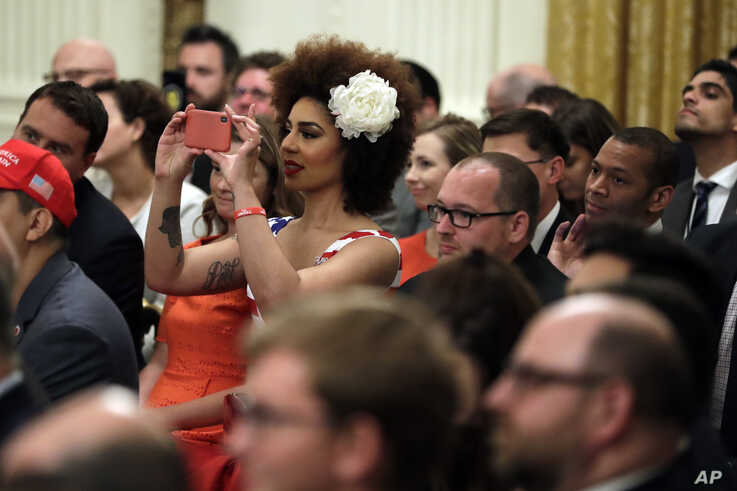 Invited guests take photos as President Donald Trump speaks during the Social Media Summit in the East Room of the White House, July 11, 2019.