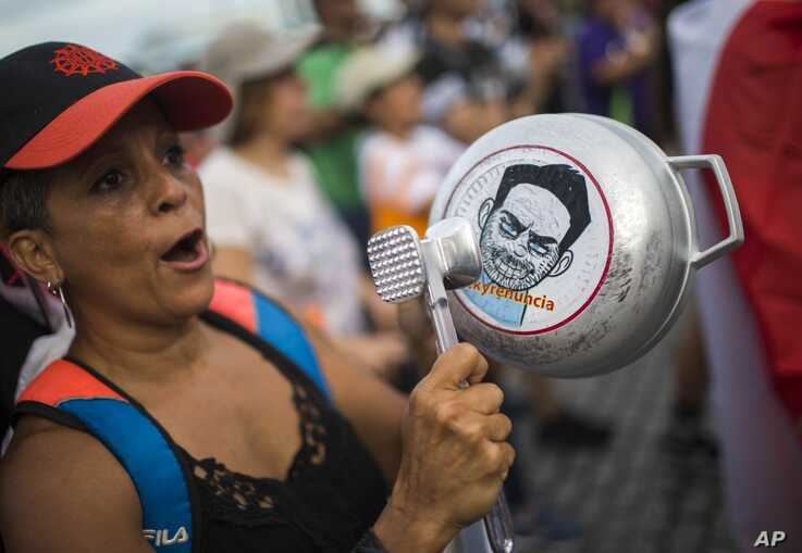 "FILE - A demonstrator bangs on a pot that has a cartoon drawing of Governor Ricardo Rossello and text the reads in Spanish ""Quit Ricky"" in San Juan, Puerto Rico, July 19, 2019."