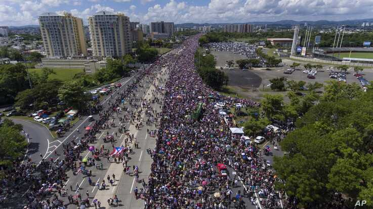 FILE - Demonstrators march on Las Americas highway demanding the resignation of Governor Ricardo Rossello, in San Juan, Puerto Rico, July 22, 2019.