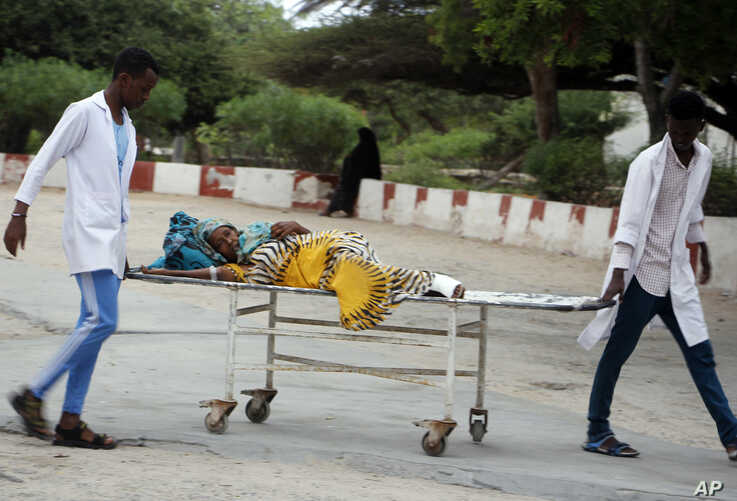 Medical workers help a civilian on a stretcher who was wounded in a suicide bombing at Madina hospital, Mogadishu, July 24, 2019.