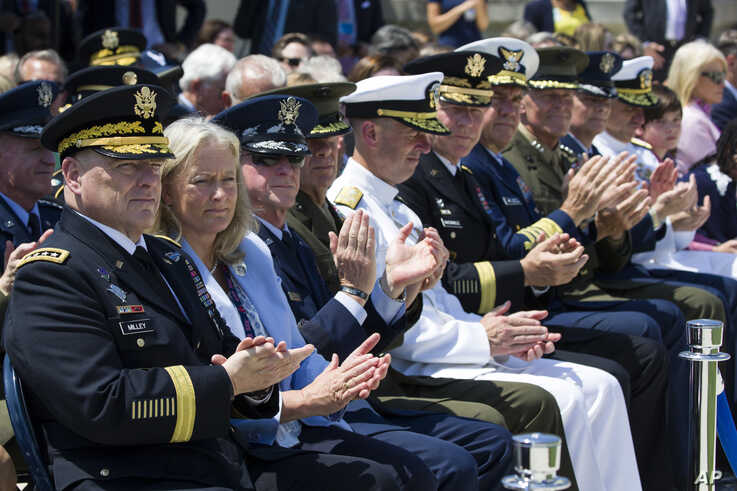 Army Chief of Staff Gen. Mark Milley, left, and others, applaud during a full honors welcoming ceremony for Secretary of Defense Mark Esper at the Pentagon, July 25, 2019.