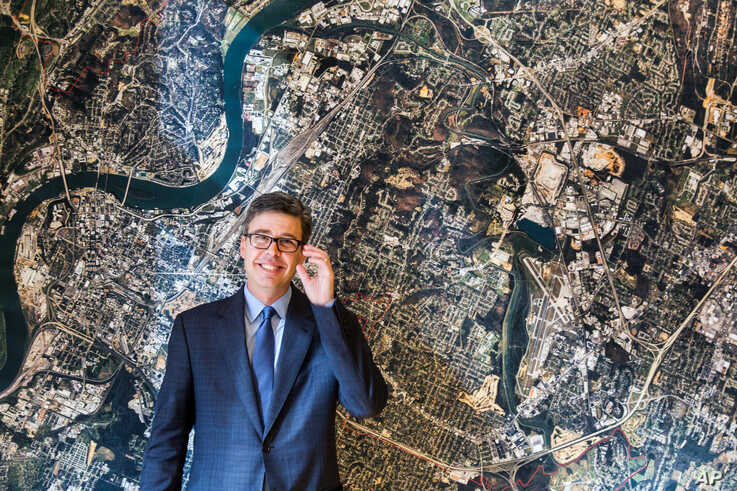 Chattanooga, Tenn., Mayor Andy Berke stands in front of an aerial image of Chattanooga, on the wall of his conference room, Nov. 17, 2014. Berke is a major promoter of the city's municipal fiber optic network that provides Internet speeds at more than 50 times the national average.