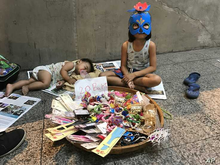A young girl sits next to a sleeping baby as she sells accessories on the sidewalk in Bangkok, Thailand.