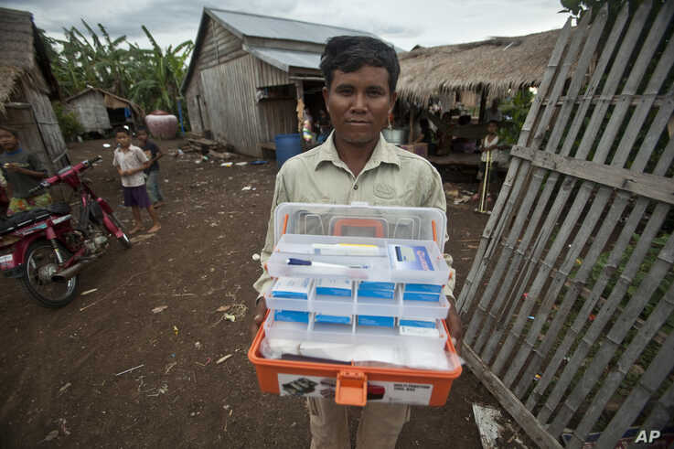 FILE - Village malaria worker Phoun Sokha, 47, shows his malaria medicine kit at O'treng village on the outskirts of Pailin, Cambodia, Aug. 29, 2009.