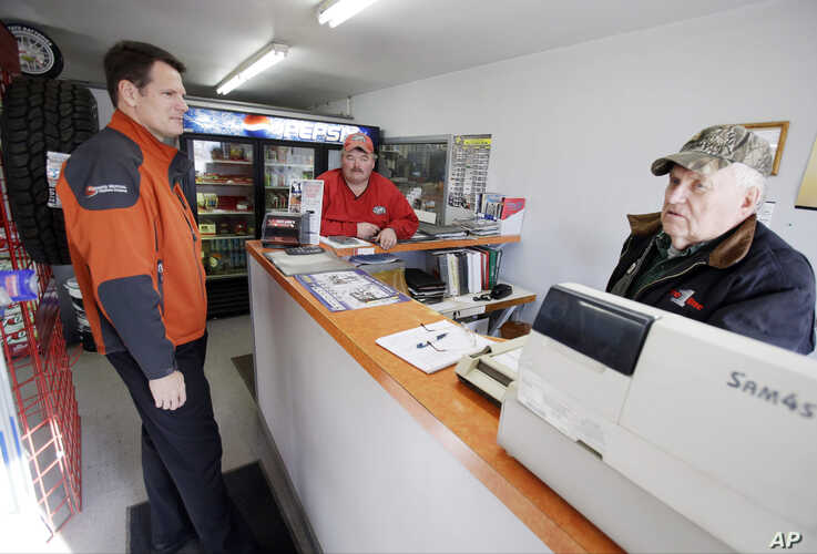 Kevin Beyer, general manager of Farmers, a century-old phone company, talks with mechanic Morrie Schacherer, center, and father Al at the auto shop they run in Dawson, Minn., Nov. 19, 2013.