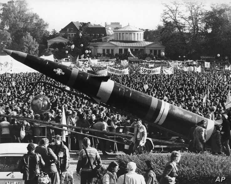 FILE - A life-size mockup of a Pershing II missile dwarfs the demonstrators protesting the scheduled deployment of missiles, in downtown Bonn, Germany, Oct. 22, 1983.