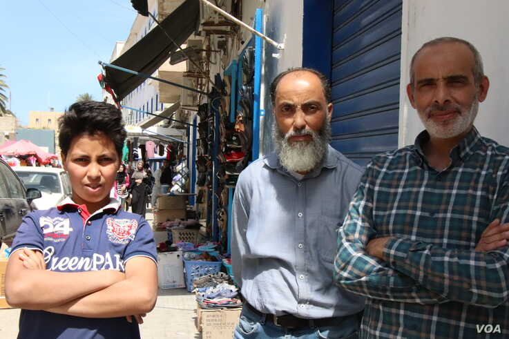 Abdullah, center, and his cousin Mohammed, right, run a shoe store in a Tripoli market, May 2, 2019.  They say that since the war began in early April, Tripoli has become poorer, more crowded and scared. (H.Murdock/VOA)