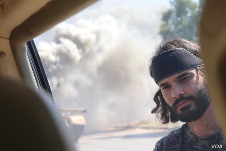 Mohammad Basheer, a fighter for Tripoli's forces, is seen next to a burning tank in Tripoli, Libya, July 7, 2019. (H.Murdock/VOA)
