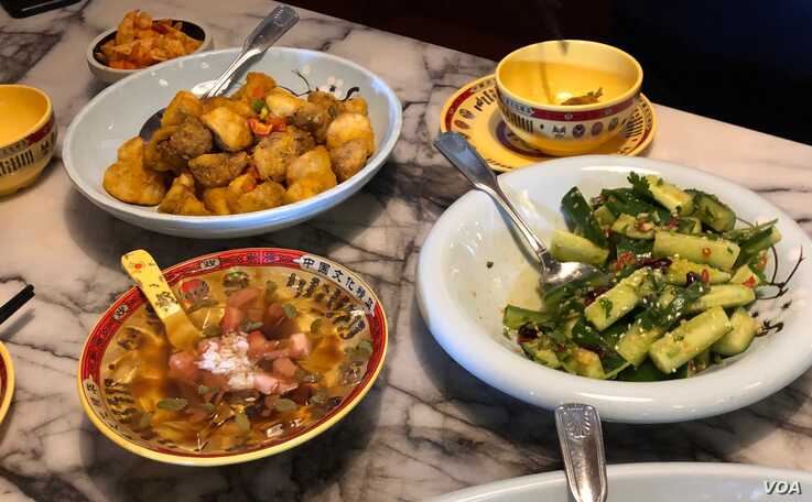 Some of the popular dishes at the Pepper Twins restaurant, clockwise from the upper left: Golden Eggplant (top), Spicy Persian Cucumber (right), Crystal Pudding (left).