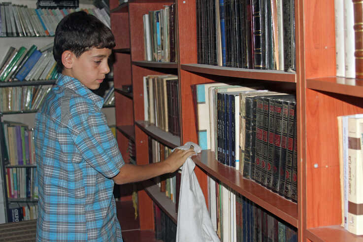 Amjad, 14, cleans shelves at the secret library in Daraya, a town in southwest Damascus, Syria. (Photo courtesy of Daraya Council Media Team)