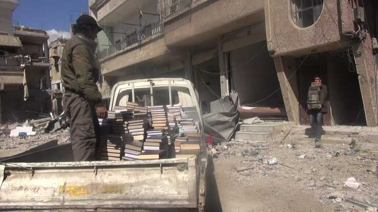Books are rescued from a bombed and abandoned building to be taken to a secret library  in the town of Daraya, Syria. (Photo courtesy of Daraya Council Media Team)