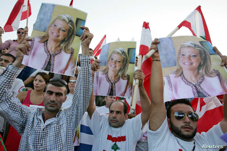 FILE - Lebanese protesters carry posters of prominent anti-Syrian news anchor May Chidiac, who was seriously wounded by a car bomb, during a sit-in at Martyrs square in Beirut, Sept. 26, 2005.