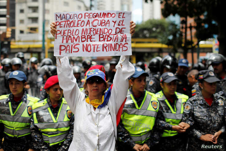 """FILE - A woman holds a sign that reads: """"Maduro gives oil to Cuba and people die of hunger. Enough. Country do not give up"""" during a protest in Caracas, Venezuela, Aug. 16, 2018."""
