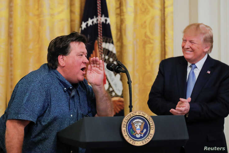 U.S. President Donald Trump applauds Bruce Hrobak, owner of Billy Bones Bait & Tackle, as he expresses his support for the president during an event touting the administration's environmental policy in the East Room of the White House, July 8, 2019.