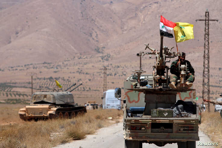 FILE - Hezbollah and Syrian flags flutter on a military vehicle in Western Qalamoun, Syria, Aug. 28, 2017.