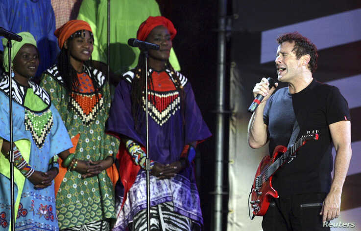 FILE - Singer Johnny Clegg, right, perfoms with the Soweto Gospel Choir at Ellispark stadium in Johannesburg, Dec. 1, 2007.