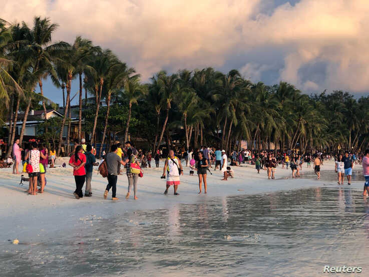 FILE - Tourists visit a beach during sunset in Boracay, Philippines, Oct. 26, 2018.