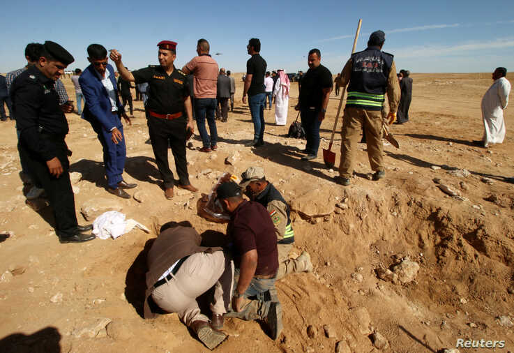 Iraqi members of the Civil Defense and Kurdish men examine an unearthed mass grave of Kurds in west of the city of Samawah, Iraq, April 14, 2019.