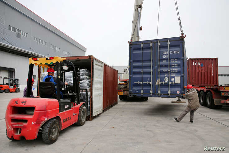 FILE - Men work on unloading the rubber imported from Belt and Road Initiative (BRI) countries at a bonded logistics center in Nantong, Jiangsu province, China, May 17, 2019.