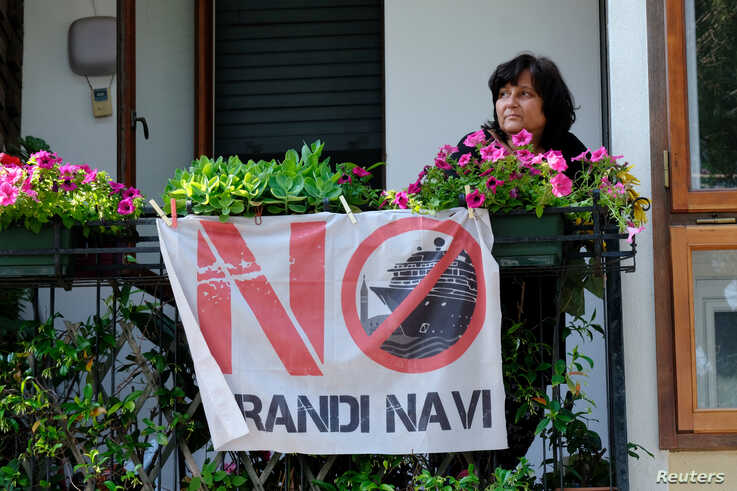"FILE - A Venetian citizen shows the flag of the movement ""No grandi navi"" (""No big ships"") to protest against the cruise ships entering the lagoon of Venice, Italy, June 3, 2019."