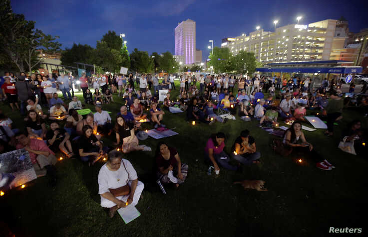 """People with candles attend as immigration rights activists hold a """"Lights for Liberty"""" candlelit vigil at Cleveland Square Park in El Paso, Texas,  July 12, 2019."""