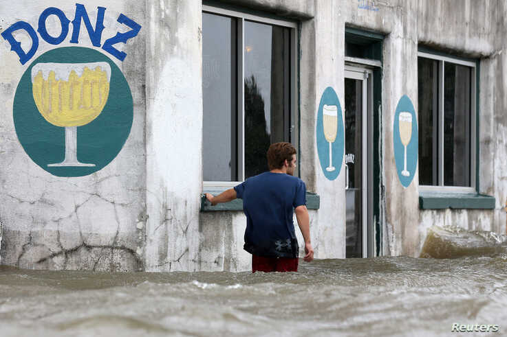 Logan Courvlle walks in front of a flooded business after Hurricane Barry in Mandeville, La.,  July 13, 2019.