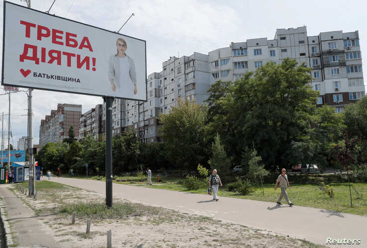 People walk past an election campaign poster with a portrait of Batkivshchyna party leader Yulia Tymoshenko ahead of the upcoming parliamentary election in Kiev, Ukraine, July 18, 2019.