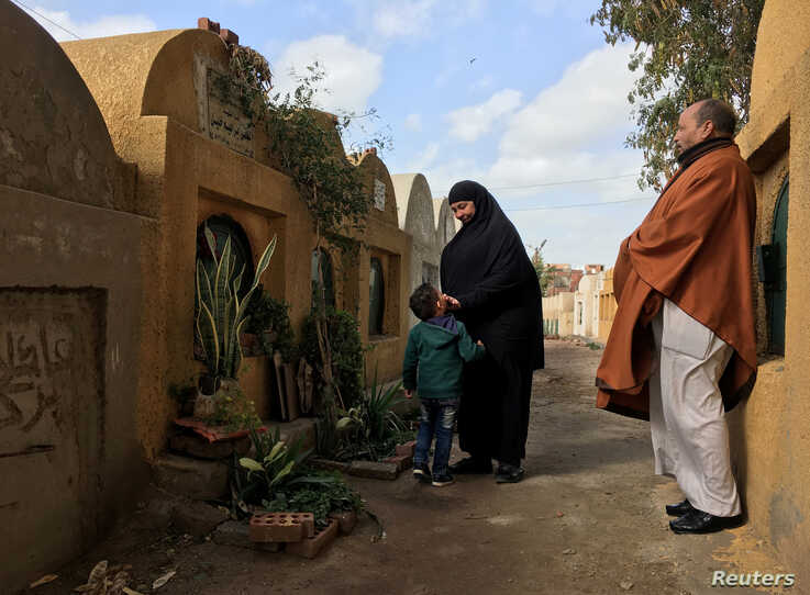 FILE - Lotfy Ibrahim's mother Tahany touches the face of a young relative during a visit to her son's grave with Lotfy's father, Khalil, near their home in Kafr al-Sheikh, Egypt, Jan. 13, 2019.