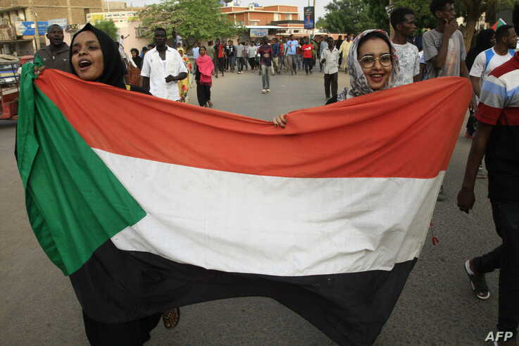Sudanese women march with a national flag during a rally in the capital Khartoum, June 30, 2019.