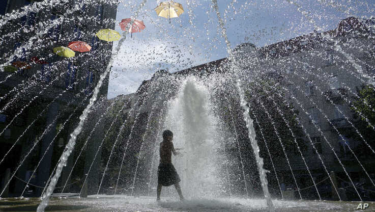 A boy plays in a fountain in Berlin, Germany,  July 24, 2019.
