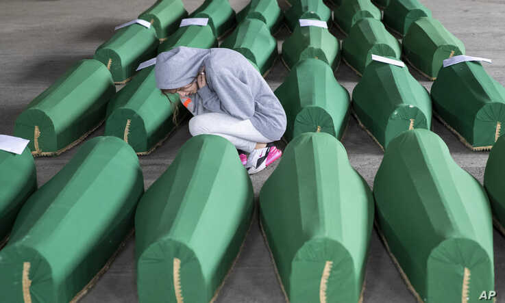 A girl inspects coffins prepared for burial, in Potocari near Srebrenica, Bosnia. The remains of 33 victims of Srebrenica massacre will be buried on July 11, 2019, 24 years after Serb troops executed some 8,000 Muslim men and boys.