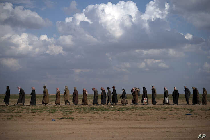Men walk to be screened after being evacuated out of the last territory held by Islamic State militants, near Baghuz, Syria, Feb. 22, 2019.