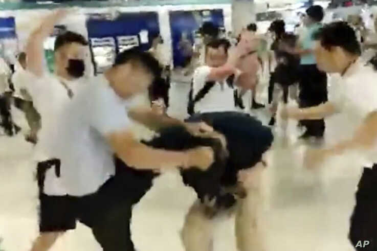 In this image taken from a video footage, white-shirted men attacked a man dressed in a black shirt at a subway station in Hong Kong, July 21, 2019. This and similar attacks brought accusations of connivance between police and criminal gangs.