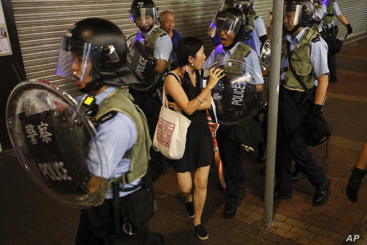 Policemen push a woman as they clear a street during a protest in Hong Kong, July 7, 2019.