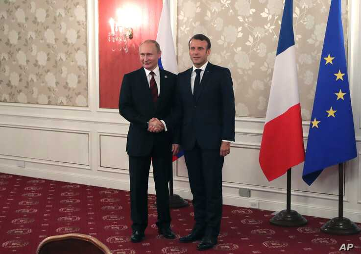French President Emmanuel Macron, right, and Russian President Vladimir Putin pose for a photo during a meeting on the sidelines of the G-20 summit in Osaka, Japan, June 28, 2019.