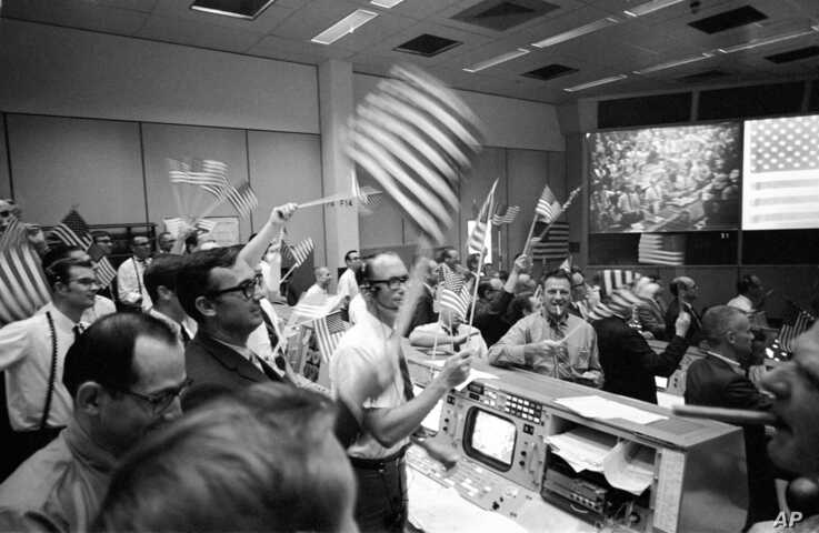 Flight controllers at the Mission Operations Control Room in the Mission Control Center at the Manned Spacecraft Center in Houston, celebrate the successful conclusion of the Apollo 11 lunar landing mission, July 24, 1969.