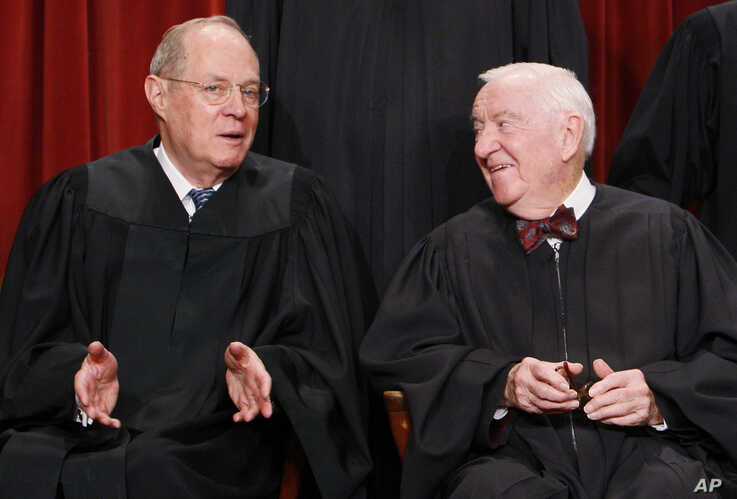 Associate Justices Anthony Kennedy, left, and John Paul Stevens talk to each other as they sit for a new group photograph with other Supreme Court judges, Tuesday, Sept. 29, 2009, at the Supreme Court in Washington.