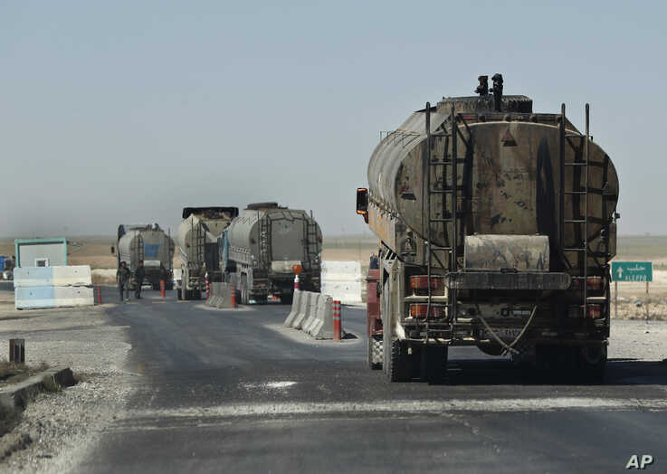 A convoy of oil tanker trucks pass a checkpoint on a highway in Hassakeh province, Syria, April 4, 2018.