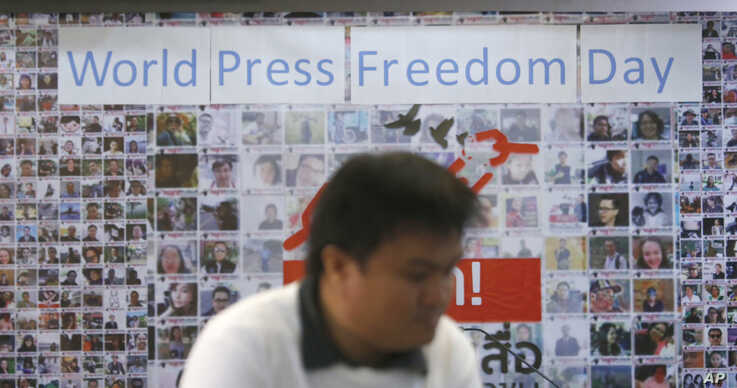 A Thai journalist walks past a banner before the International World Press Freedom Day a press conference in Bangkok, Thailand, May 3, 2017.