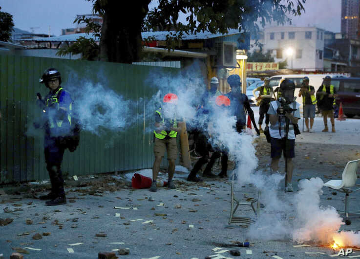 Journalists work near tear gas canisters deployed during a face-off between police and protesters at the Yuen Long district in Hong Kong on Saturday, July 27, 2019.