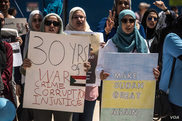 Protesters hold signs at a rally in support of the Sudan's revolution, in Chicago, Illinois, June 29, 2019. (J. Patinkin/VOA)