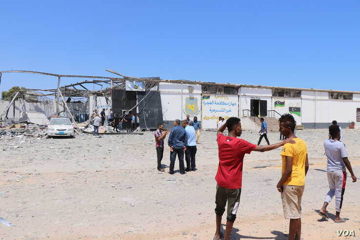 Hours after the bombing of the detention center that killed more than 50 civilians and wounded more than 130, migrants watch authorities search for human remains, near Tripoli, Libya, July 3, 2019. (H. Murdock/VOA)