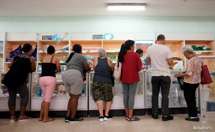 FILE - People wait in line to buy goods in a state store in downtown Havana, Cuba, May 10, 2019.
