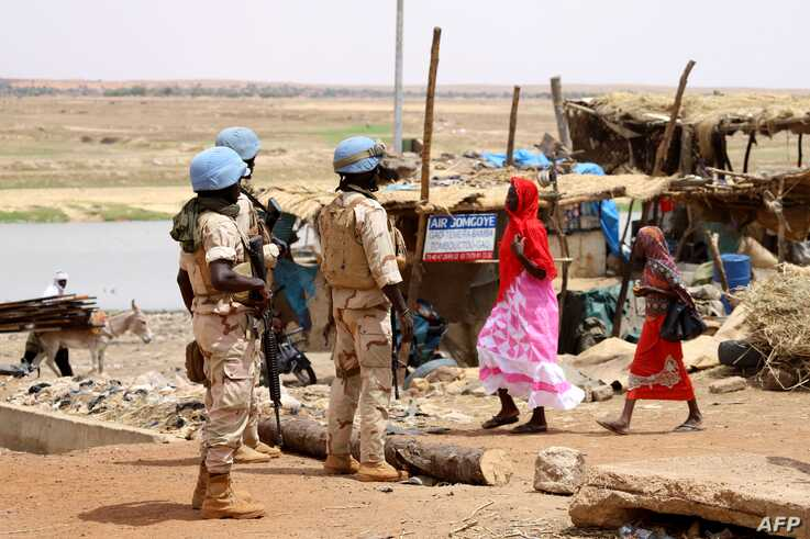 FILE - Senegalese soldiers of the U.N. peacekeeping mission in Mali MINUSMA (United Nations Multidimensional Integrated Stabilization Mission in Mali) patrol on foot in the streets of Gao, July 24, 2019, a day after a suicide bomb attack.